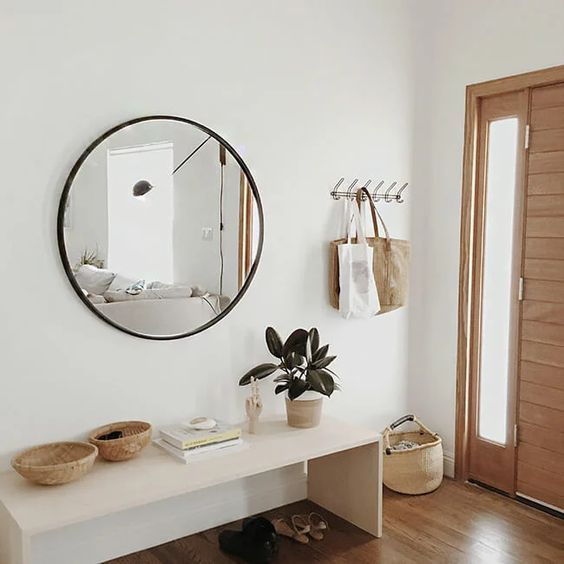 a modern entry with a sleek bench, a round mirror, some baskets and a clothes rack is stylish and looks ethereal