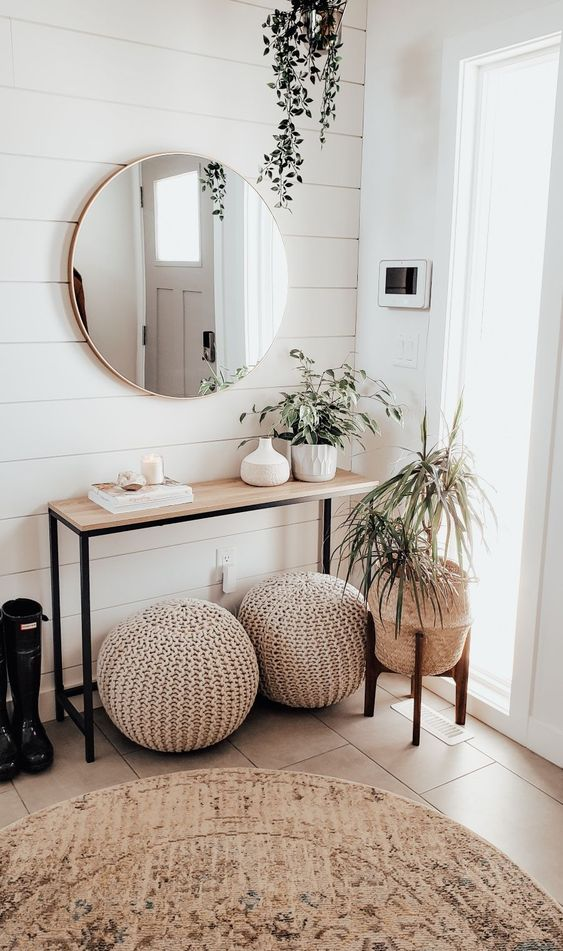 a neutral modern entryway with a wooden console, crochet ottomans, potted plants and a round mirror is chic