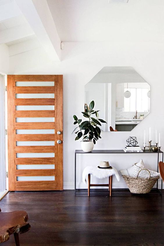 a simple modern entryway with a geometric mirror, a black console, stools and a basket with pillows