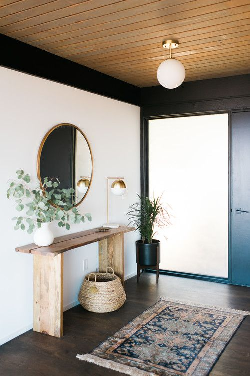 a stylish modern entryway with a round mirror, a basket, a plant on a stand and a boho rug