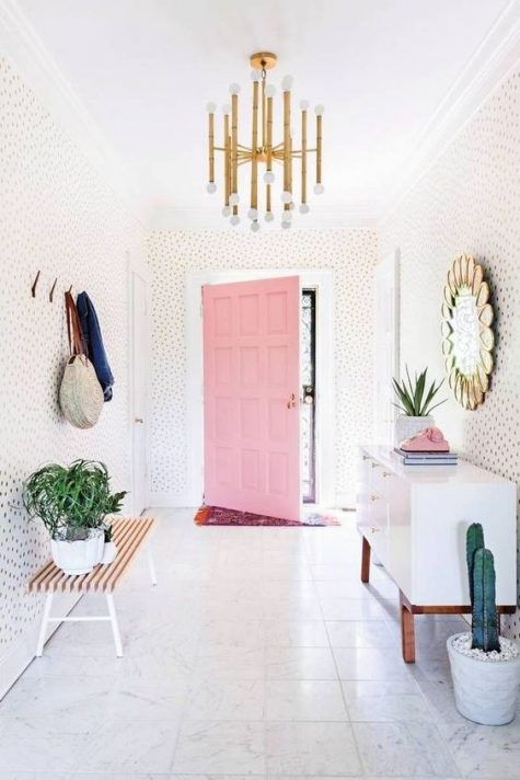 a modern playful and whimsical entryway with polka dot walls, a white sideboard, a bench, clothes racks and a mirror