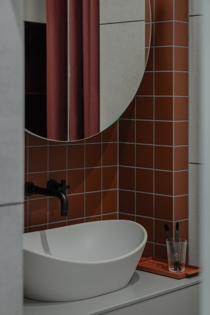 The bathroom is done with rust-colored tiles, a round mirror and a vessel sink