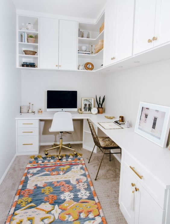 a mid-century modern home office in white, with a corner desk and cabinets in it, cabinets over the desk and a bright and fun rug