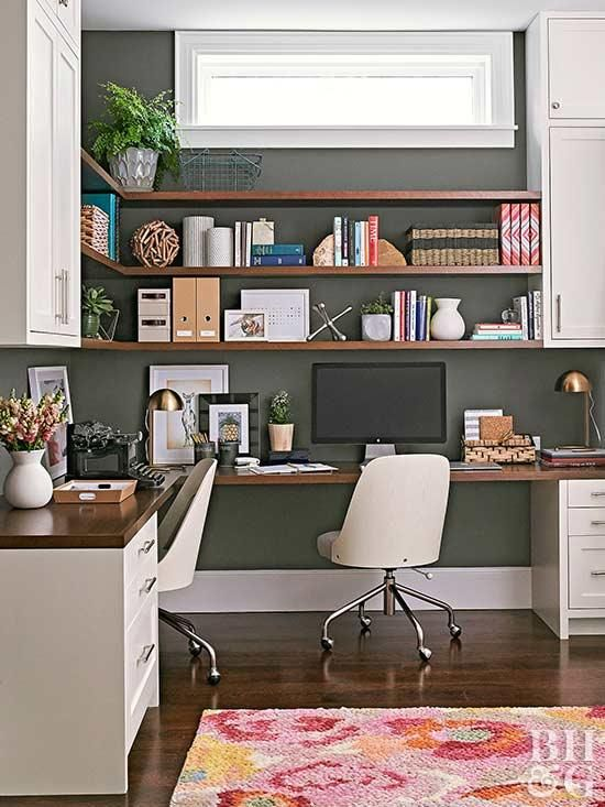 a mid-century modern home office with a black wall, a corner desk and open shelves with closed storage units plus chic white chairs