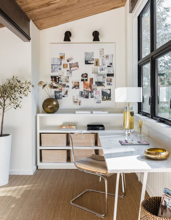 a stylish and refined home office with a corner desk and open storage units, a jute rug and an acrylic chair is very chic