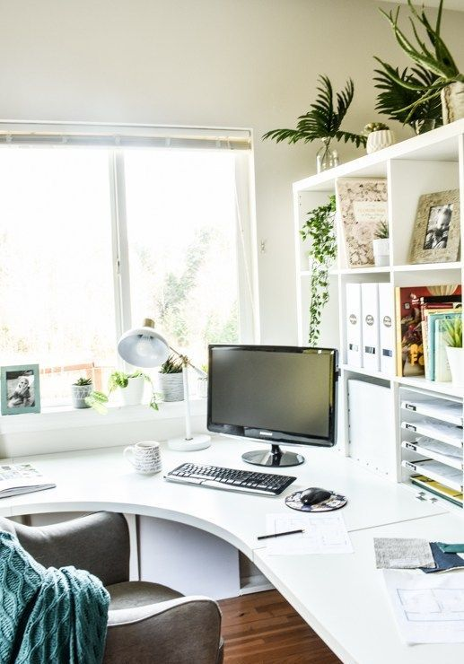 a stylish contemporary home office in white, with a curved corner desk and open storage unit, a comfy chair and some greenery