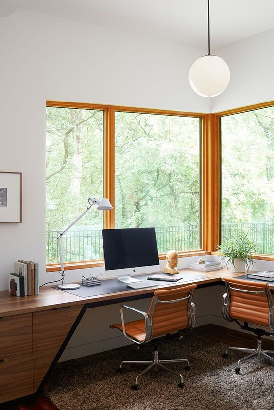 an elegant mid-century modern home office with a chic wooden corner desk, leather chairs and large windows to enjoy the views