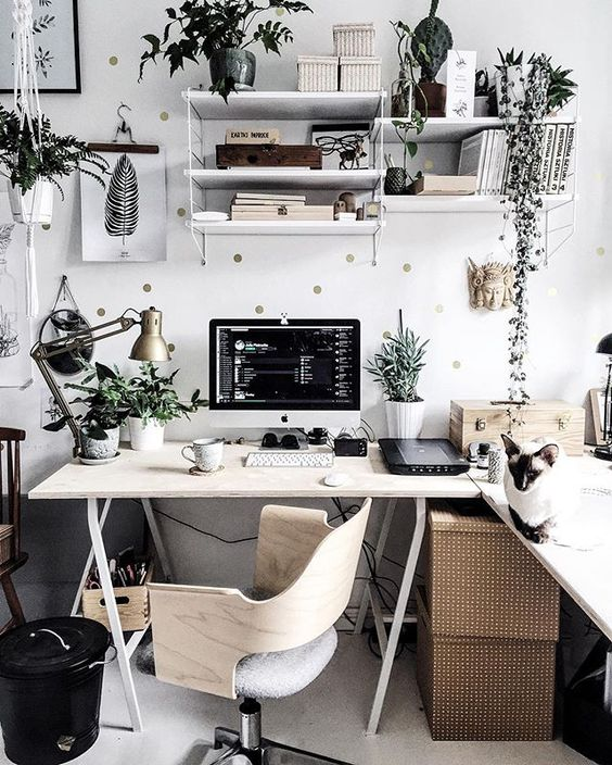 a stylish Scandinavian home office with a trestle corner desk, boxes, greenery, a polka dot wall and a plywood chair