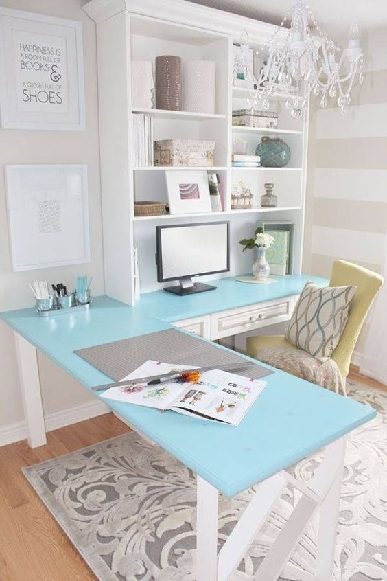 a vintage farmhouse home office with a blue corner desk and a storage unit on one side, a yellow chair and a glam crystal chandelier
