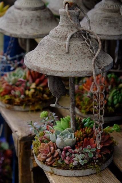 a concrete lantern with succulents and greenery and some chains for outdoor decor
