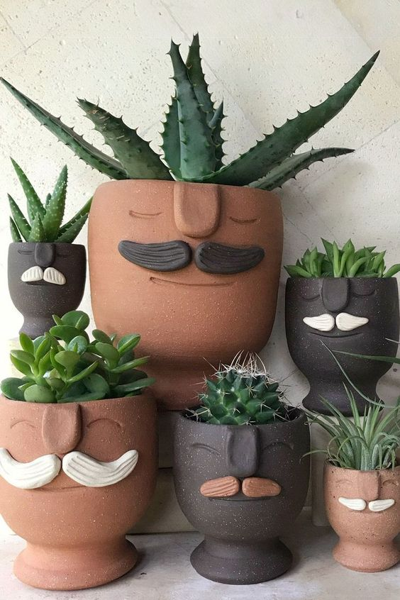 quirky terracotta and black planters with moustaches and succulents are a fun and bold idea to rock