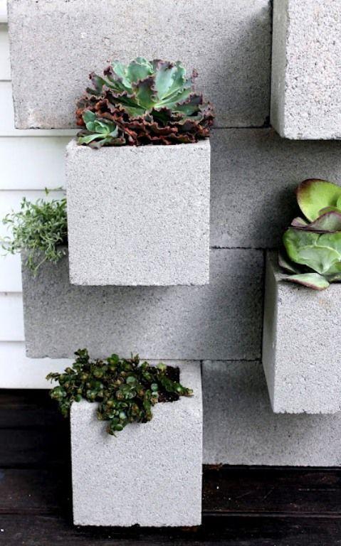 a cement wall with built-in planters with greenery and succulents is a stylish outdoor decoration to go for