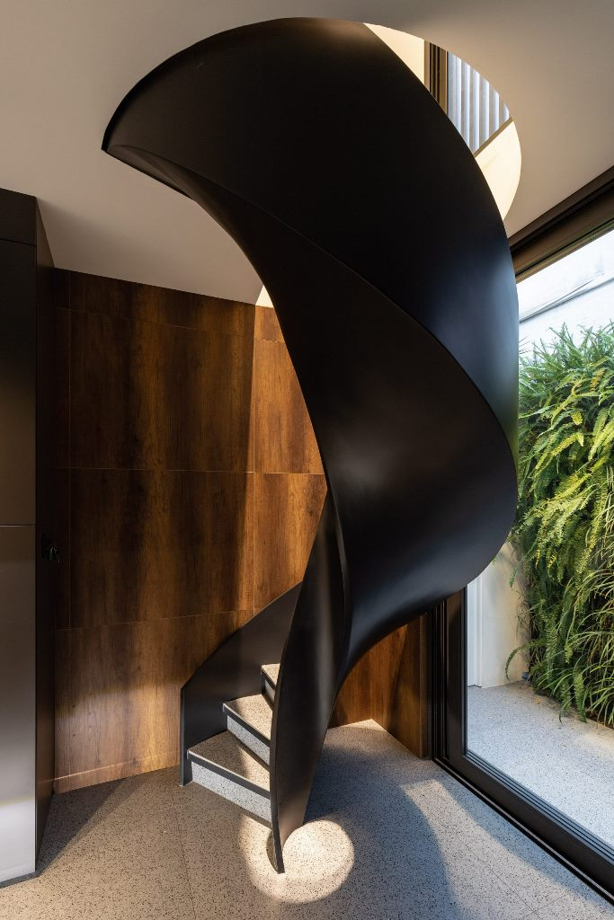 A black spiral staircase features in the kitchen