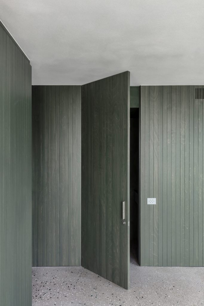 The same green stain has been applied across the apartment's wood-panelled walls