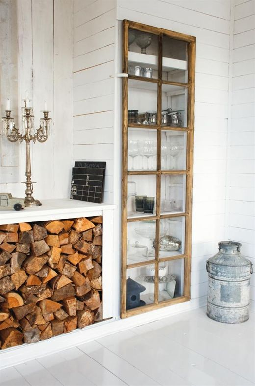 a built-in storage unit with a glass door made of old window frames is a stylish idea for a rustic space