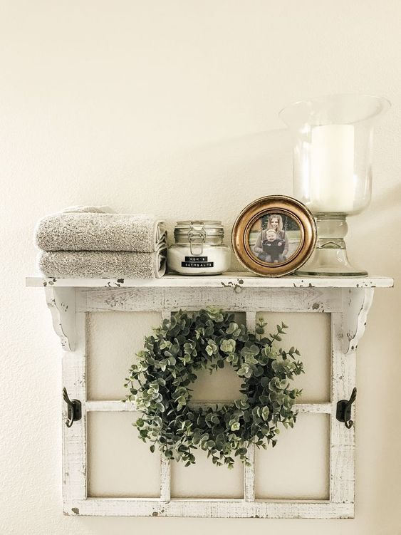a cool and easy shelf of an old window frame, with a greenery wreath, a candle, a photo, some blankets is ideal for a bathroom