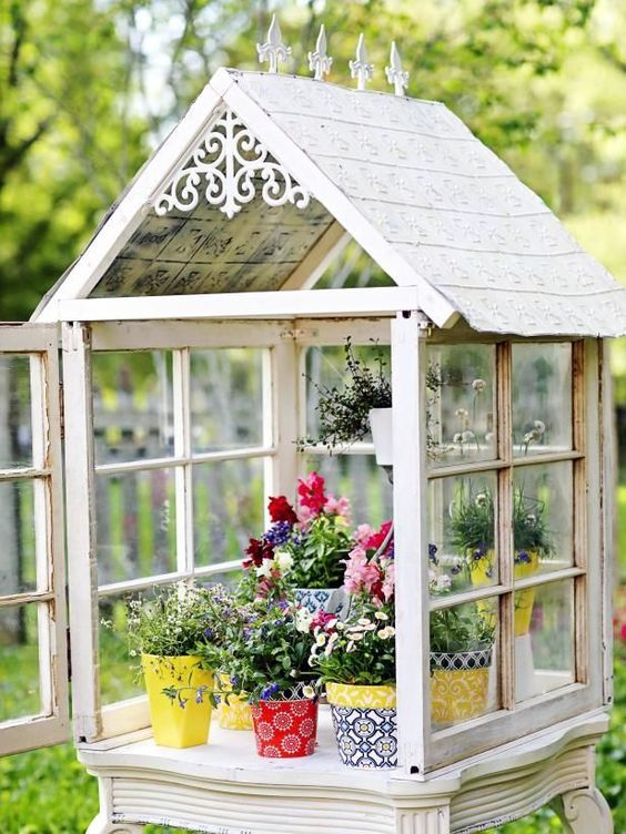a small greenhouse made of old window frames, with bright planters and greenery and flowers is a cool DIY
