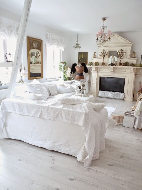 a catchy shabby chic living room in white, with a tan fireplace, vintage chandeliers, a mirror and lace curtains