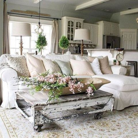 a neutral shabby chic living room with a white sectional, a low shabby table, greenery and blooms is welcoming