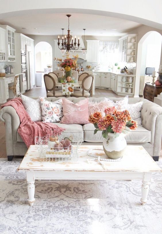 A Shabby Chic Living Room With A Grey Sofa, A White Shabby Table, Pink Pillows And Blankets And Blooms