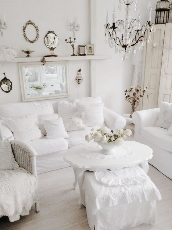 a pure white shabby chic living room with stylish furniture, a crystal chandelier, mirrors and candles is wow