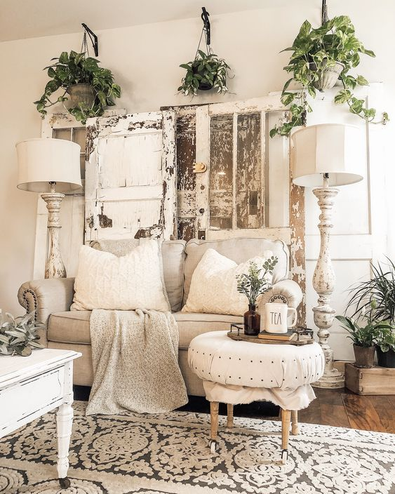 a neutral shabby chic living room with stylish furniture, potted greenery, shabby shutters and tall floor lamps