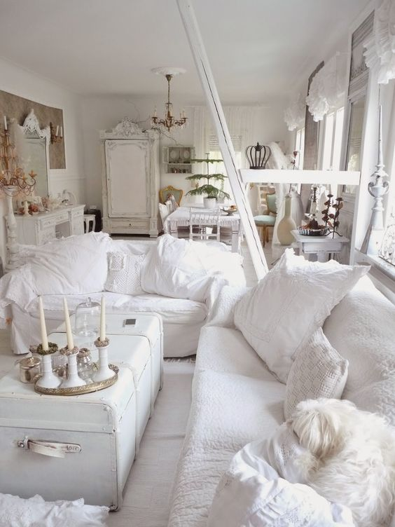 a white shabby chic living room with chic furniture, a white chest, white pillows and candles is very elegant