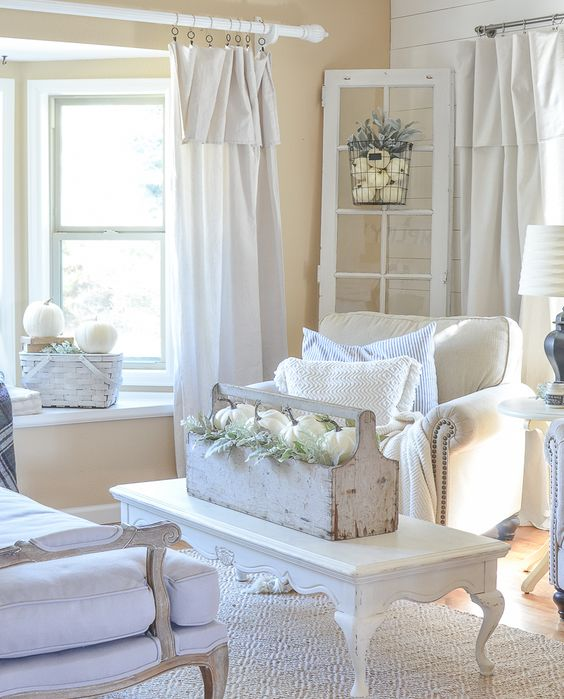 a white shabby chic space with elegant furniture, a low table, a toolbox with blooms and white pumpkins