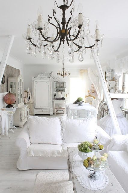 A White Shabby Chic Living Room With Sofas, A Crystal Chandelier And A Dining Zone A Bit Further Done With A Cohesive Look