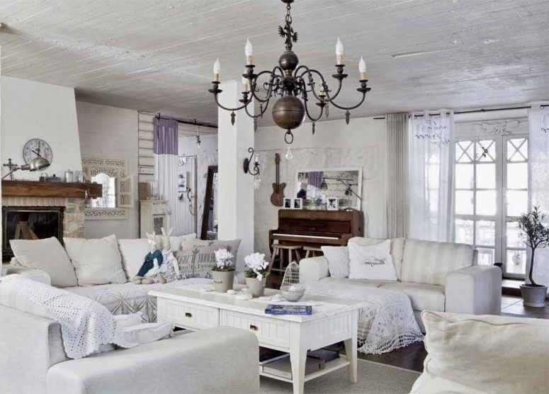 A White Shabby Chic Living Room With Elegant Furniture, A Vintage Chandelier, A Low Table, A Fireplace In Stone And Crochet And Doilies