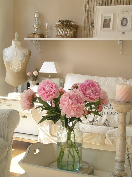 a romantic shabby chic living room in neutrals, with simple and elegant furniture, an open shelf, some art and candles and blooms