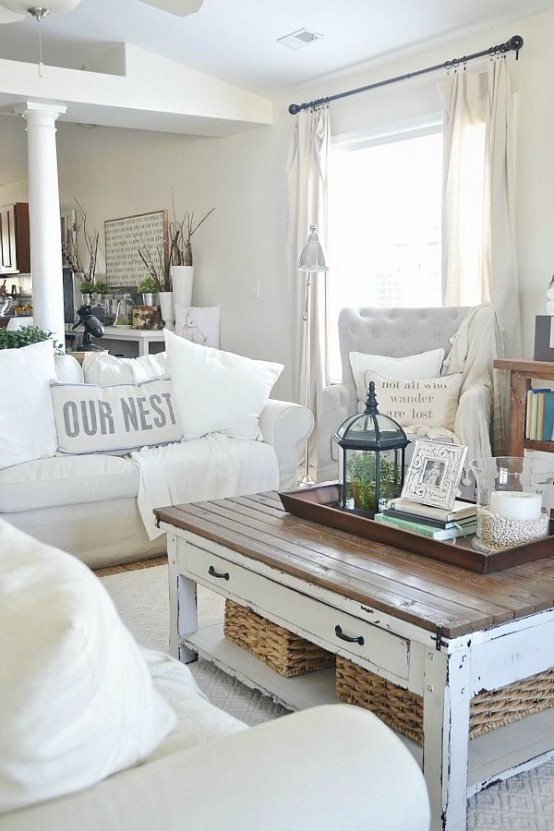 a neutral farmhouse shabby chic living room with white furniture, a low table, various baskets and table lamps is very stylish