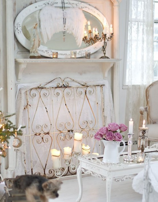 a white shabby chic living room with a non-working fireplace covered with a screen, an oval mirror and refined furniture