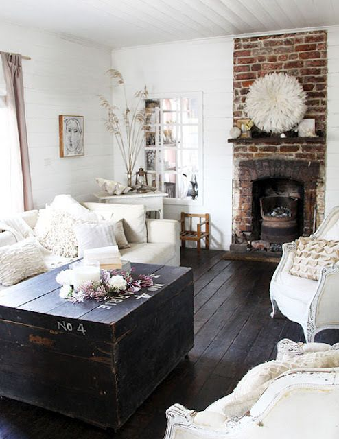 a shabby chic living room in neutrals, with a brick fireplace, a dark chest table, neutral textiles and pillows seems cozy and welcoming