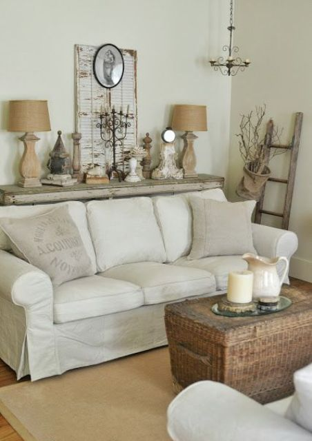 a neutral shabby chic living room with simple and rustic furniture, a woven chest, some table lamps and decor and vintage shutters