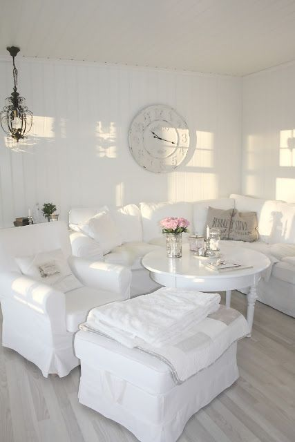 a white shabby chic living room with refined furniture, a white table, a clock and a crystal chandelier is very elegant