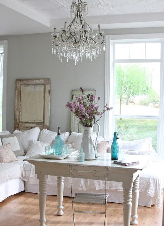 a white shabby chic living room with vintage furniture, a crystal chandelier, blue vases, blooms and a mirror