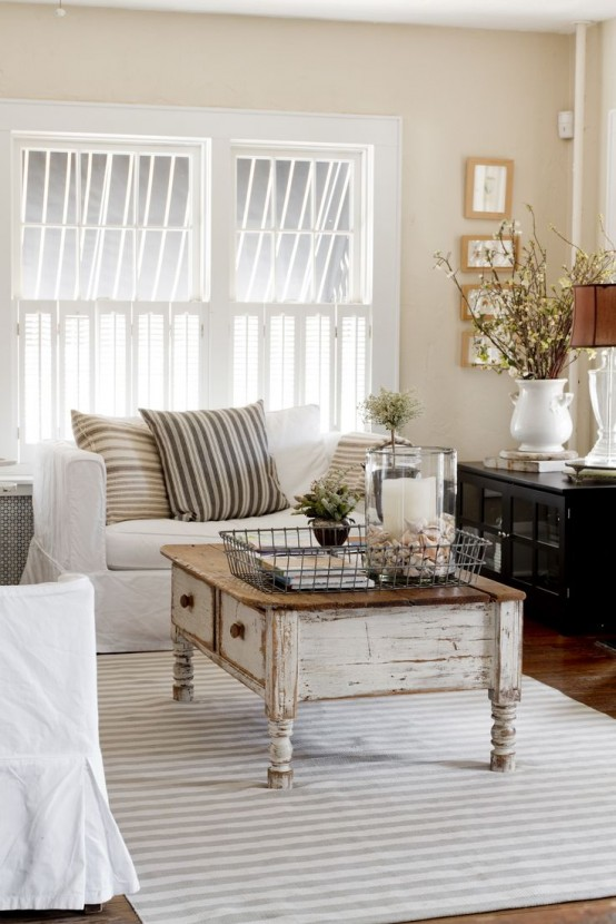 a farmhouse shabby chic living room with black and white furniture, striped pillows, greenery and a gallery wall