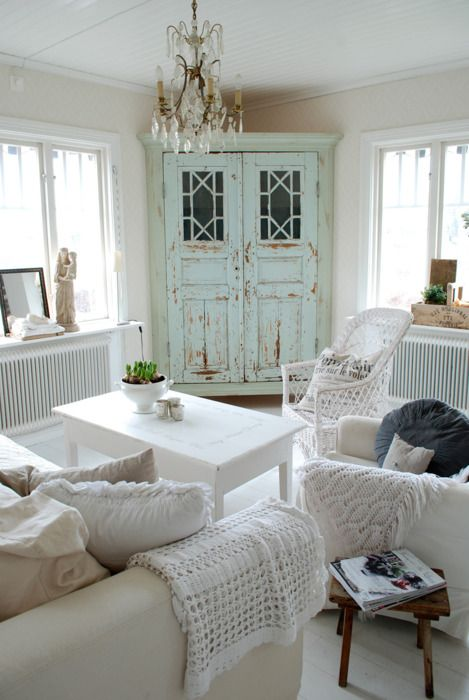a shabby chic living room in neutrals, with a mint cabinet, a crystal chandelier, crochet and knit blankets and pillows