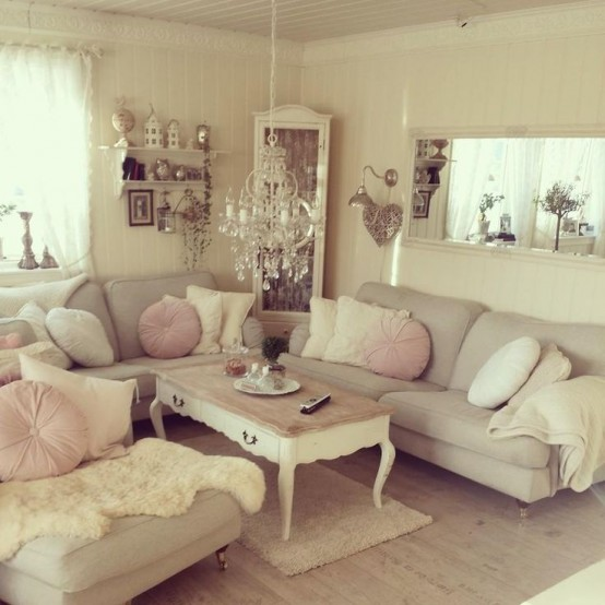 a neutral and whitewashed shabby chic living room with simple and elegant furniture, a low table and pendant lamps