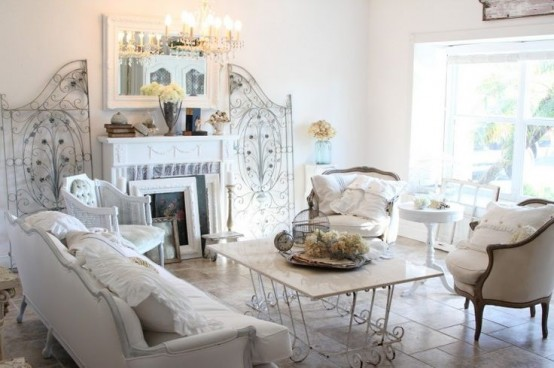 a neutral shabby chic living room with elegant furniture, a fireplace, a crystal chandelier, some screens and a table