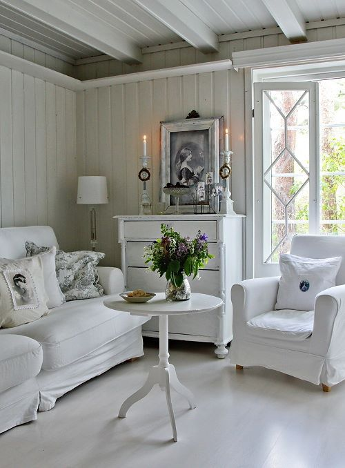 A Neutral Shabby Chic Living Room With Elegant And Chic Furniture, A White Sideboard, Candles And Potted Plants Is Very Stylish