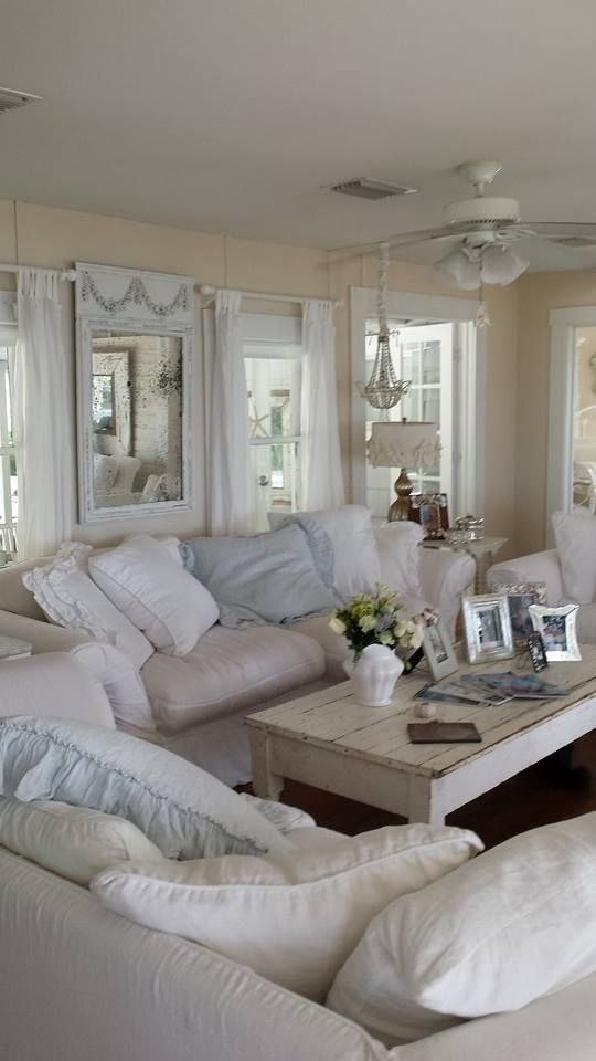 A Neutral Shabby Chic Living Room With Warm-Colored Walls, Neutral Furniture And Pillows, A Beaded Chandelier And Pastel Touches Here And There