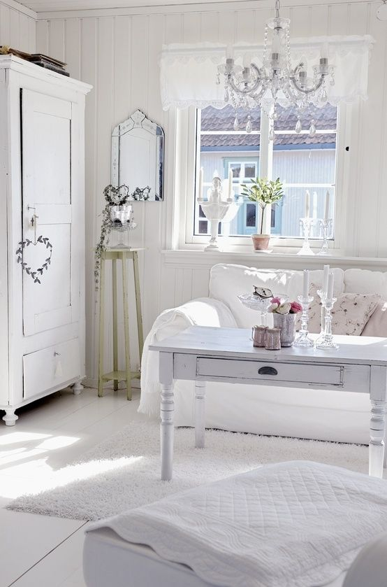 A White Shabby Chic Living Room With Whitewashed Furniture, A Crystal Chandelier, Potted Greenery And Plants And Floral Pillows