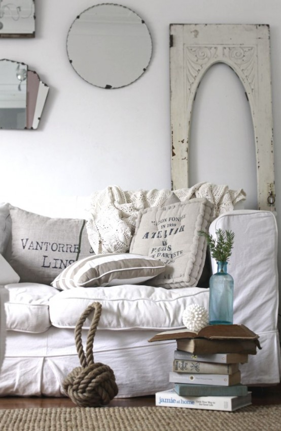 A White Shabby Chic Living Room With Cool Furniture, A Gallery Wall With Mirrors, A Jute Rug, Some Blooms In A Vase Is Beautiful