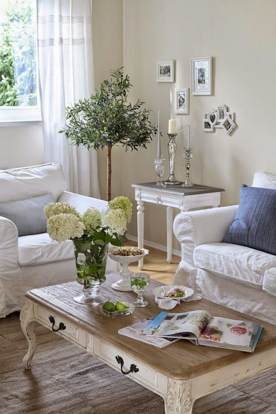a refined shabby chic living room in neutrals, with white furniture, a low table, blue pillows and potted greenery