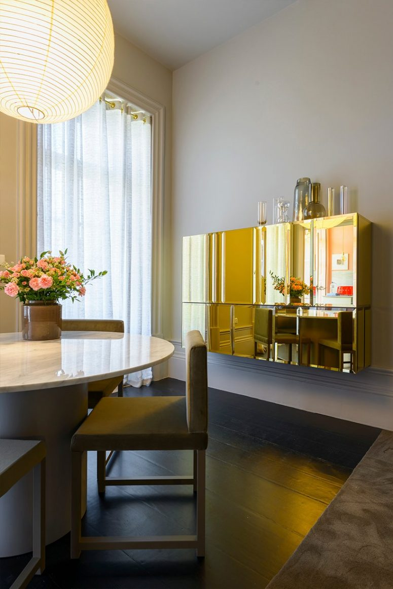 The dining room is very refined, with a round table with a marbel tabletop, chic chairs and a gorgeous polished gold cabinet on the wall