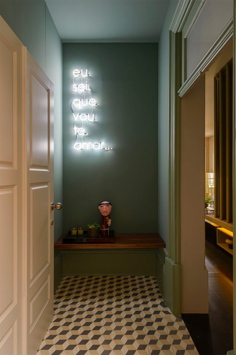 The entryway is done with green walls, a geometric floor, a bench and a neon sign and it looks bold and whimsy