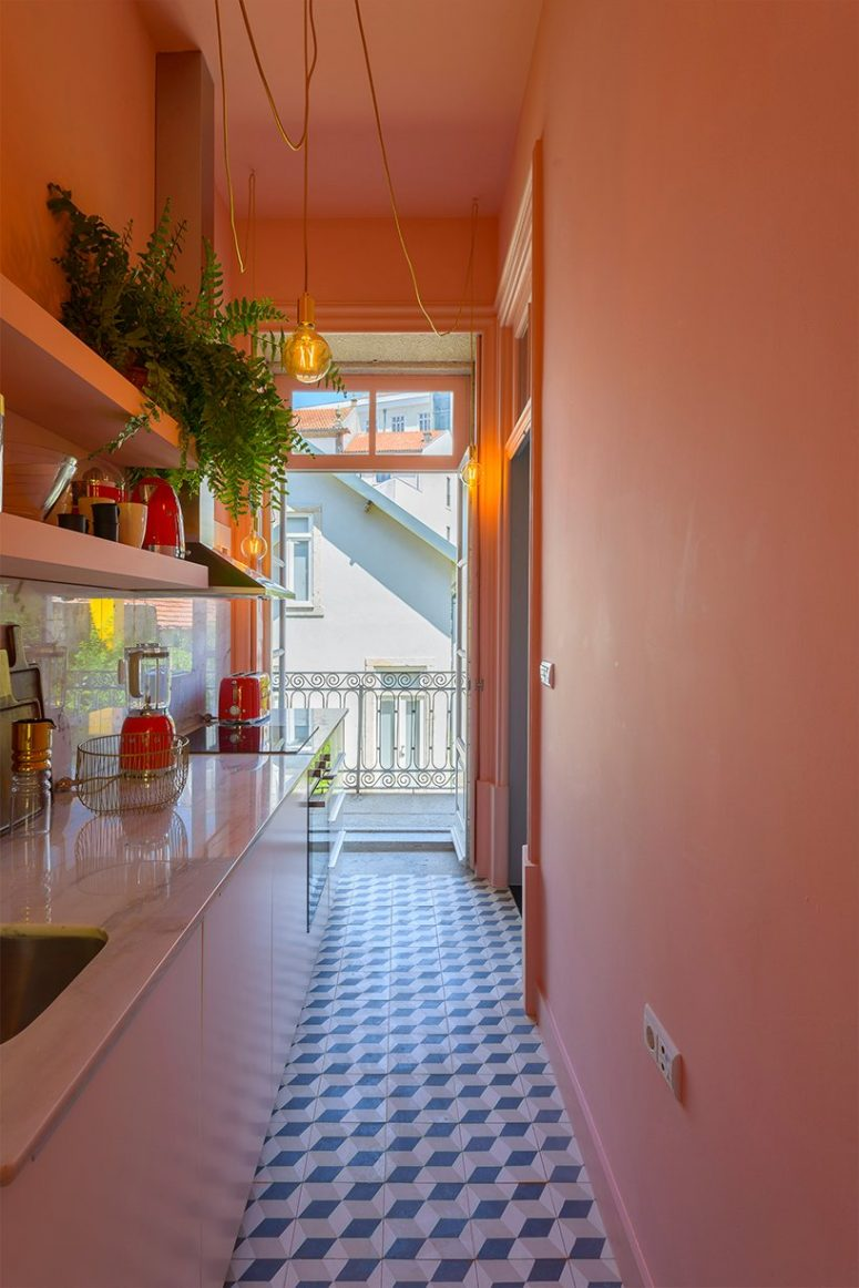 Red appliances and other touches add color to the kitchen, and a balcony entrance fills it with natural light
