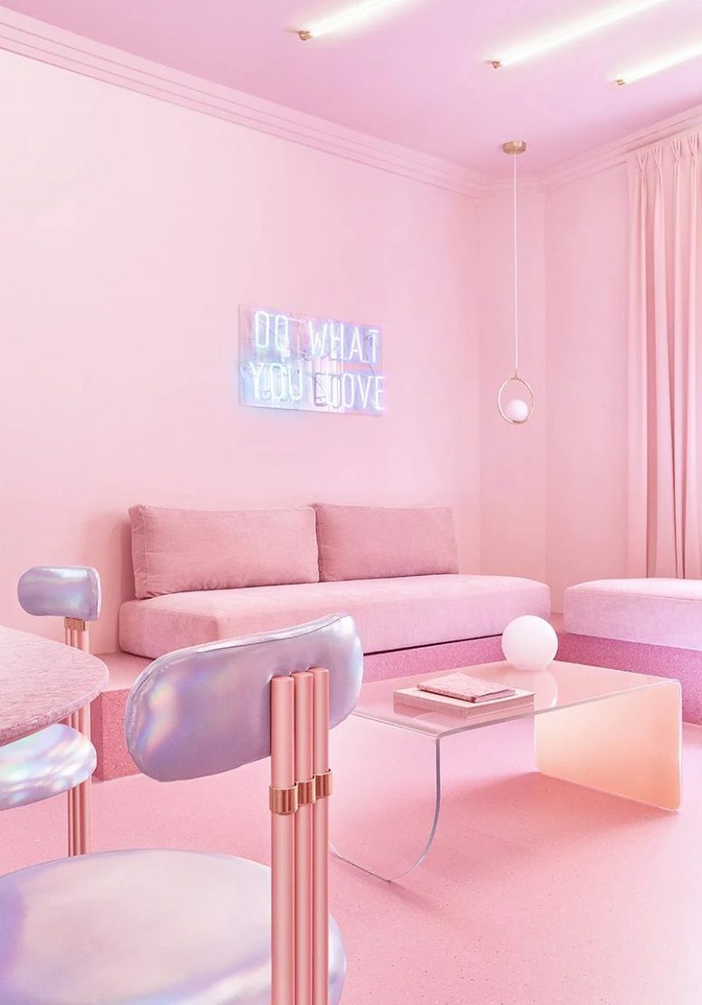 The living room is done with pink furniture put on pink stone, iridescent chairs, a neon sign, pendant lamps and an acrylic table, lights on the ceiling